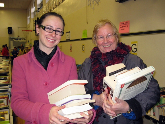 "Barbara Lance (right), of Mayfair Avenue, invited daughter Elizabeth Lance, now of Gatineau, to BookFest. ""I wouldn't miss this for anything,"" says Elizabeth. Barbara says: ""I bought murder mysteries for summer reading, and non-fiction coffee table books to support my family history habit."" Elizabeth tracked down novels, books about dogs and business books, including Seth Godin's <em>Purple Cow</em>, but says she's most looking forward to rereading John Grogan's <em>Marley and Me.</em> ""I already have this in digital format, but there's no substitute for a real book."" Photo by Denise Deby."