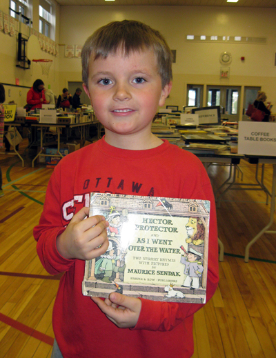 """Liam Edwards, 7, of Westboro, picked up a book of nursery rhymes by Maurice Sendak. """"I remember it from when I was a kid,"""" says mom and BookFest volunteer Kim Edwards."""
