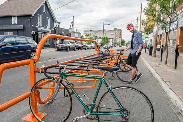 There's no missing Kitchissippi's new bike corrals. Hintonburg's Chris Harlock locks up his bike. Photo by Ted Simpson.