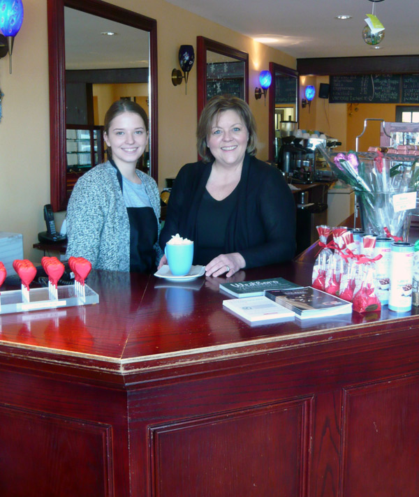 Retail associate Chelsea Chapman (L) and Cococo store owner Céline Levo with a cup of the house-made hot chocolate. Photo by Heather Heagney