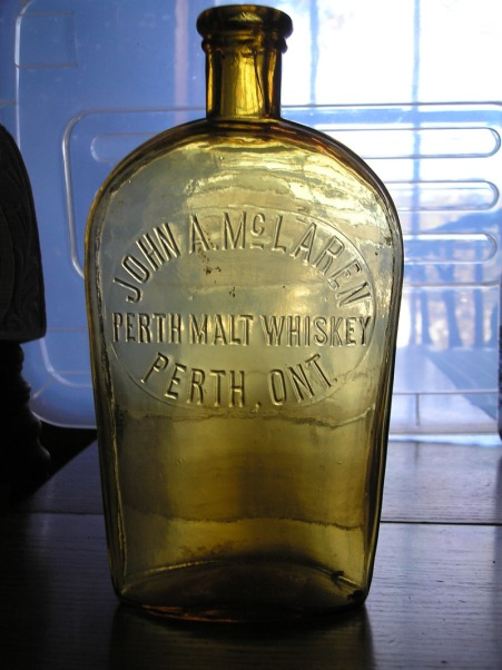 John A. McLaren distilled whiskey in Perth, 50 miles west of Ottawa in the 1880's and his products became very popular in hotels in that town and neighbouring communities. The amber colour of this bottle makes it a rare find and valued at $300.