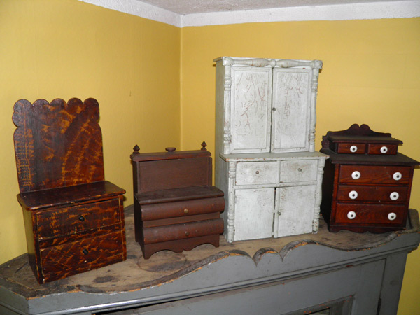 "From left to right: a miniature chest of drawers with scalloped backboard (16""H / 8.5 W/ 6""D) from Renfrew County; a sewing stand,  (10""H / 6""W / 4"" D) from Western Ontario; white child's china cupboard (24""H / 13""W / 9""D) from Renfrew County; chest of drawers with original porcelain knobs (13""H / 8.5""W /12""D) from Eastern Ontario. Photo courtesy of Shaun Markey"